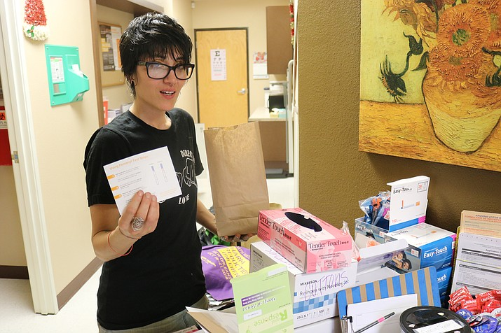 Dusti Yamaguchi of Kingman Harm Reduction and Sonoran Prevention Works stands next to the wide variety of resources available to the community at 3505 Western Ave. (Photo by Travis Rains/Daily Miner)