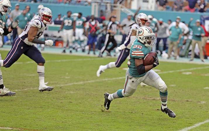 Miami Dolphins running back Kenyan Drake (32) runs for a touchdown during the second half of an NFL football game against the New England Patriots, Sunday, Dec. 9, 2018, in Miami Gardens, Fla. The Dolphins defeated the Patriots 34-33. (Charles Trainor Jr./Miami Herald via AP)