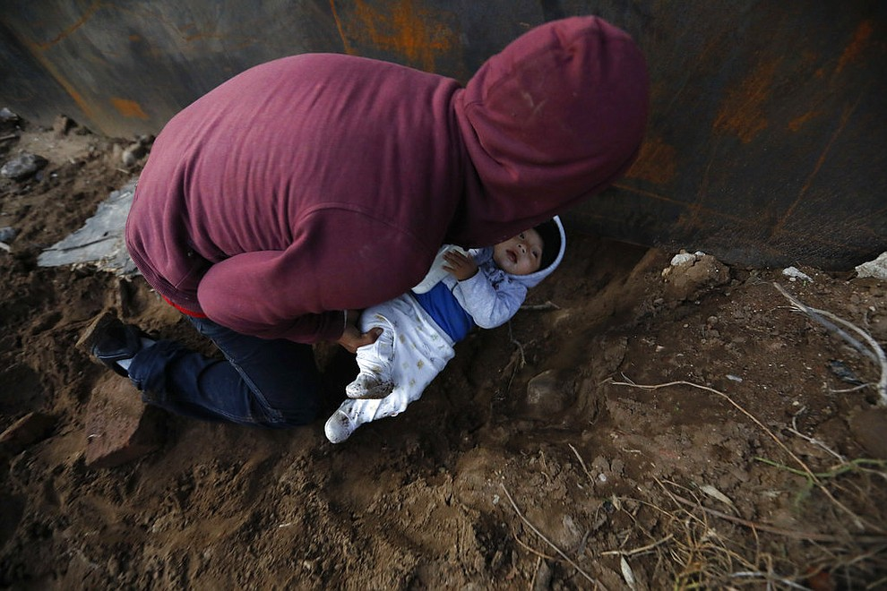 Honduran migrant Joel Mendez, 22, passes his eight-month-old son Daniel through a hole under the U.S. border wall to his partner, Yesenia Martinez, 24, who had already crossed in Tijuana, Mexico, Friday, Dec. 7, 2018. Moments later Martinez surrendered to waiting border guards while Mendez stayed behind in Tijuana to work, saying he feared he'd be deported if he crossed. (AP Photo/Rebecca Blackwell)