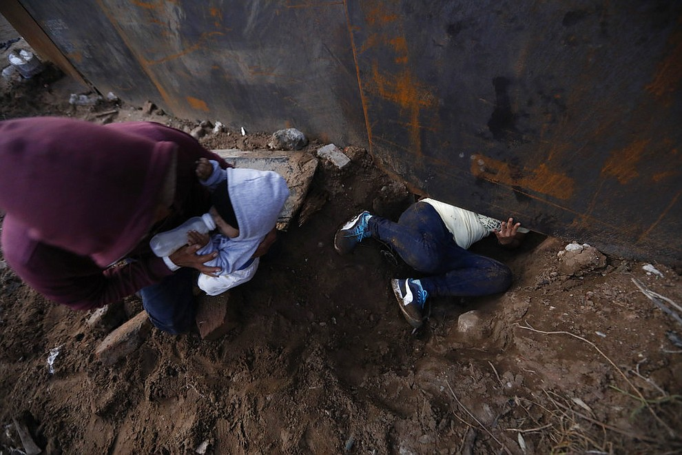 Honduran migrant Joel Mendez, 22, feeds his eight-month-old son Daniel as his partner Yesenia Martinez, 24, crawls through a hole under the U.S. border wall, in Tijuana, Mexico, Friday, Dec. 7, 2018. Moments later Martinez surrendered to waiting border guards while Mendez stayed behind in Tijuana to work, saying he feared he'd be deported if he crossed. (AP Photo/Rebecca Blackwell)