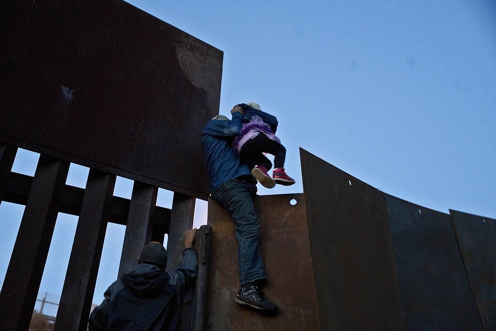 A Honduran migrant helps a young girl cross to the American side of the border wall, in Tijuana, Mexico, Sunday, Dec. 2, 2018. In November, President Donald Trump issued a proclamation suspending asylum rights for people who try to cross into the U.S. illegally from Mexico, although a divided U.S. appeals court has refused to immediately allow the Trump administration to enforce the ban. (AP Photo/Ramon Espinosa)
