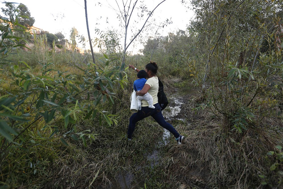 Yesenia Martinez, 24, carries her eight-month-old son Daniel as she looks for a place to cross the U.S. border wall to surrender to border patrol and request asylum, in Tijuana, Mexico, Friday, Dec. 7, 2018. Martinez surrendered to waiting border guards while her partner Joel Mendez stayed behind in Tijuana to work, saying he feared he'd be deported if he crossed. (AP Photo/Rebecca Blackwell)