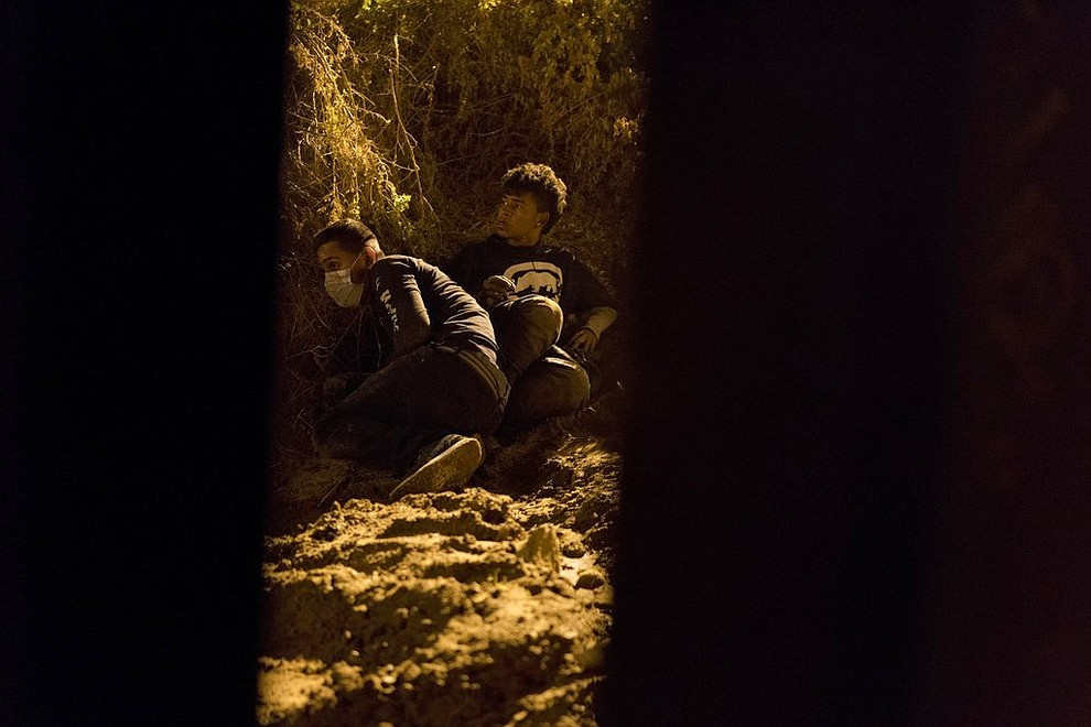 Salvadoran migrant Cesar Jobet, right, and Daniel Jeremias Cruz hide from U.S. border agents after they dug a hole in the sand under the border wall and crossed over to the U.S. side, in Playas de Tijuana, Mexico, Friday, Nov. 30, 2018. When the two youths were detected by agents they ran back to the Mexican side. (AP Photo/Ramon Espinosa)