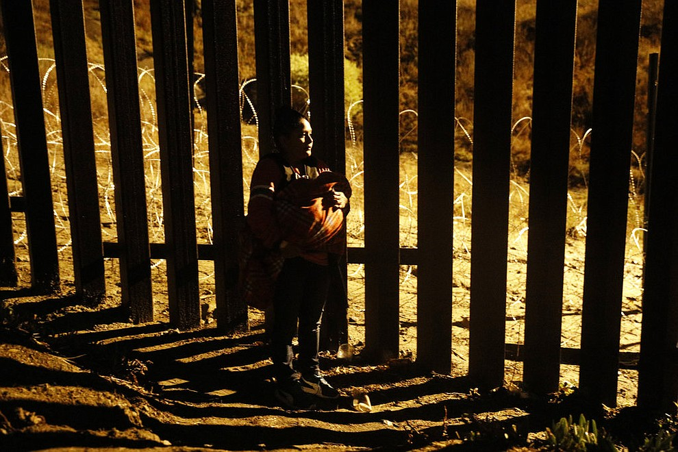 A woman holding a baby peers through the U.S. border fence as she tries to reach a point where scores of migrants have been crossing in recent days, now blocked by private security, in Playas de Tijuana, Mexico, Wednesday, Dec. 5, 2018. Legal groups argue that federal law states that immigrants can apply for asylum no matter how they enter U.S. territory. (AP Photo/Rebecca Blackwell)