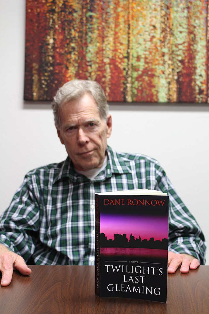 "Kingman's Dane Ronnow shows a copy of his book, ""Twilight's Last Gleaming,"" a thriller about the nation's electrical grid and infrastructure being completely shut down after a nuclear attack. The book goes on sale Saturday for $14 on Amazon. (Photo by Hubble Ray Smith/Daily Miner)"