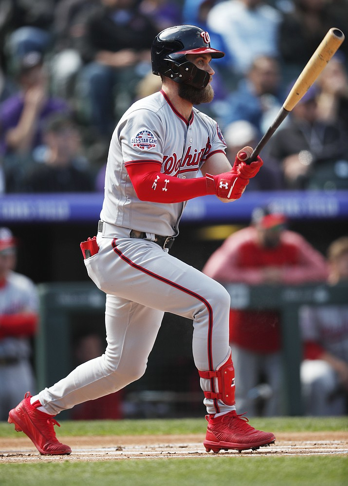 In this Sept. 30, 2018, file photo, Washington Nationals' Bryce Harper grounds into a double play against the Colorado Rockies in the first inning of a baseball game in Denver. Paul Goldschmidt and Robinson Cano have already switched teams this offseason, going to the Cardinals and Mets in major trades. As for Manny Machado and Harper - the jewels of the free agent market - they're still waiting. (David Zalubowski/AP, File)