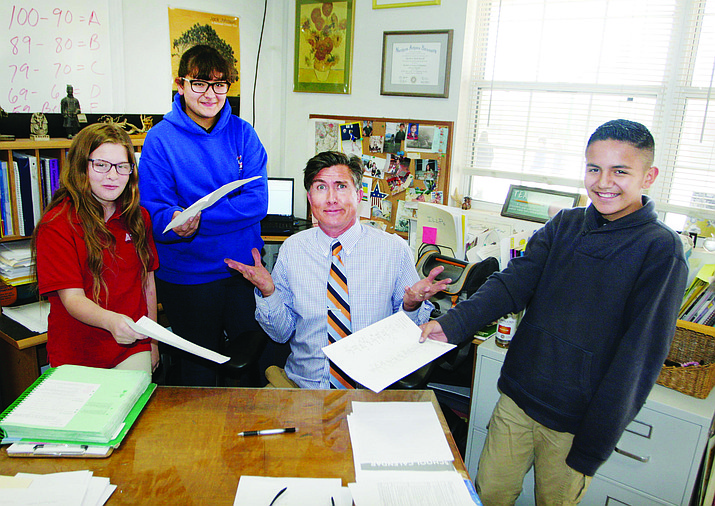 Kimberley Brady, Thalia Rocha and Diego Gonzalez, from left, sixth grade students at Cottonwood's American Heritage Academy, turn in their assignments to teacher Matt Bazzill. VVN/Bill Helm
