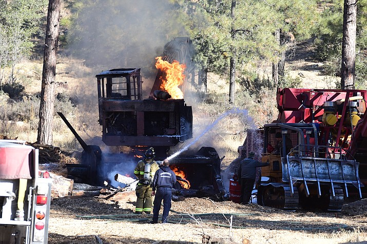 Firefighters tamp down a small wildfire after a log loader exploded into flames about five miles southwest of Prescott Tuesday morning, Dec. 11.