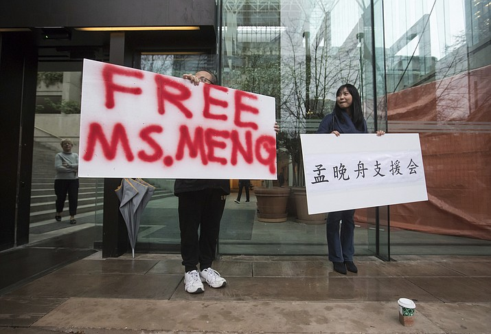 Supporters hold signs outside the British Columbia Supreme Court in Vancouver during the third day of a bail hearing for Meng Wanzhou, the chief financial officer of Huawei Technologies, on Tuesday December 11, 2018. (Darryl Dyck/The Canadian Press via AP)