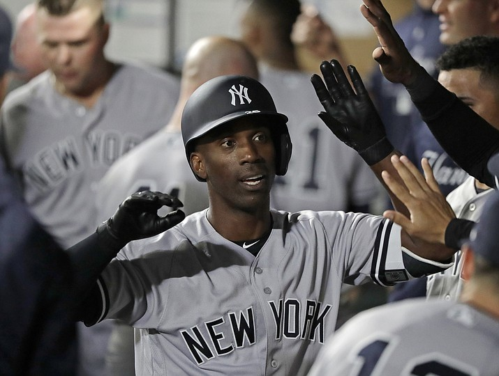 In this Sept. 7, 2018, file photo, New York Yankees' Andrew McCutchen is greeted in the dugout after he hit a two-run home run during the third inning of a baseball game against the Seattle Mariners, in Seattle. A person familiar with the negotiations tells The Associated Press that All-Star outfielder Andrew McCutchen and the Philadelphia Phillies have agreed to a $50 million three-year contract. The person spoke on condition of anonymity Tuesday, Dec. 11, 2018, because the agreement, which includes a club option for 2022, is subject to a successful physical.(Ted S. Warren/AP, File)