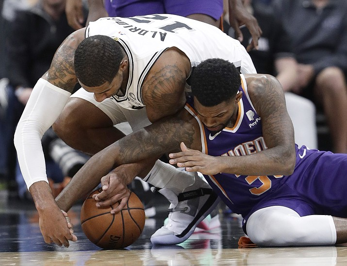 San Antonio Spurs forward LaMarcus Aldridge (12) and Phoenix Suns guard Troy Daniels (30) scramble for a loose ball during the first half of an NBA basketball game, Tuesday, Dec. 11, 2018, in San Antonio. (Eric Gay/AP)