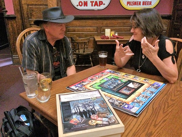 """Julie Trainor, right, tests her new board game, Whiskey Row, this past August at the Palace Saloon with Brad Courtney, left, author of """"Prescott's Original Whiskey Row,"""" and Danny Romero, longstanding Palace musician. Trainor will host a launch party for the game at 3 p.m. Sunday, Dec. 16, at the Palace. (Sue Tone/Courier)"""