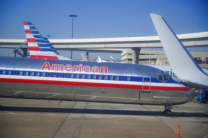 In this Nov. 2018 file photo, American Airlines aircraft are serviced at Dallas/Fort Worth International Airport, in Texas.  A man is suing both American Airlines Inc. and SkyWest Airlines Inc after he says one of his pinky fingers was caught in an airline armrest mechanism for nearly an hour during a flight to Los Angeles. (AP Photo/Mike Stewart)