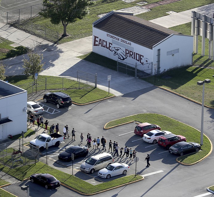 Students are evacuated by police from Marjory Stoneman Douglas High School Wednesday, Feb. 14, 2018, in Parkland, Fla., after a shooter opened fire on the campus. There were plenty of missteps in communication, security and school policy before and during the Florida high school massacre that allowed the gunman to kill 17 people. (Mike Stocker/South Florida Sun-Sentinel via AP, File)