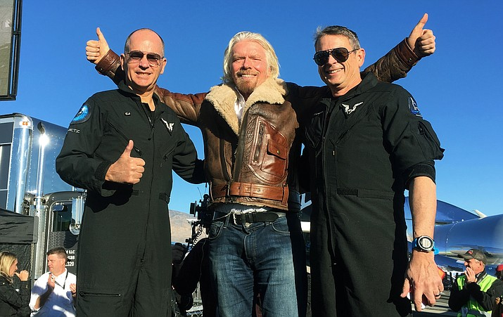 "Richard Branson center celebrates with pilots Rick ""CJ"" Sturckow, left, and Mark ""Forger"" Stucky, right, after Virgin Galactic's tourism spaceship climbed more than 50 miles high above California's Mojave Desert on Thursday, Dec. 13, 2018. (John Antczak/AP)"