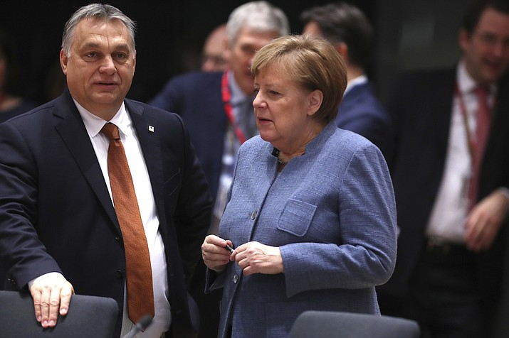 German Chancellor Angela Merkel, right, speaks with Hungarian Prime Minister Viktor Orban during a round table meeting at an EU summit in Brussels, Friday, Dec. 14, 2018. (AP Photo/Francisco Seco)