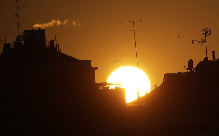The sun sets over buildings in Milan, Italy, Friday, Dec. 14, 2018. The climate change conference, COP24, is closing today in Katowice, Poland. (Luca Bruno/AP)