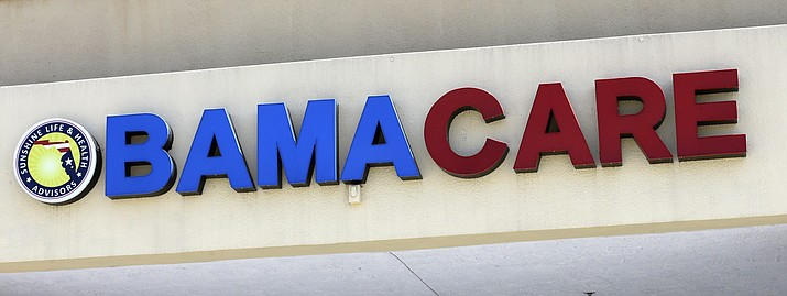 This May 11, 2017, file photo shows an Obamacare sign being displayed on the storefront of an insurance agency in Hialeah, Fla. (AP Photo/Alan Diaz, File)