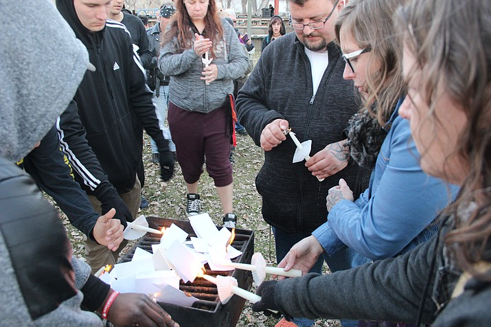 Participants of a candlelight vigil hosted in Prescott Wednesday, Dec. 12, burn papers that have the names of people who have died due to drugs or alcohol. (Max Efrein/Courier)