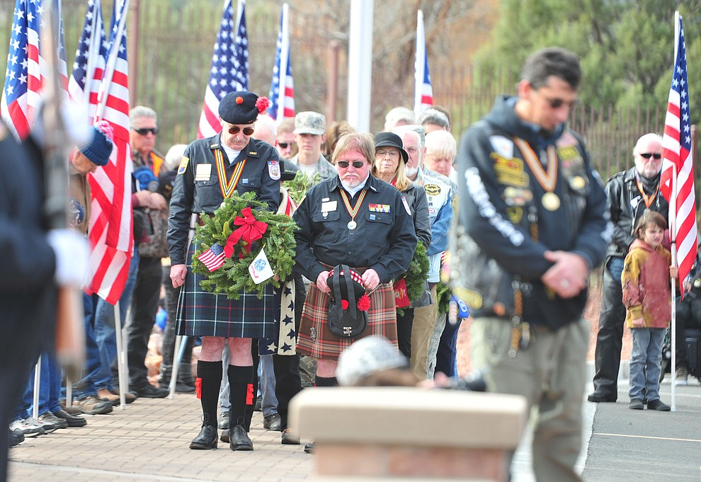 People pray during the Wreaths Across America ceremony where 2106 veteran remembrance wreaths at the Prescott National Cemetery Saturday, Dec. 15, 2018. (Les Stukenberg/Courier).