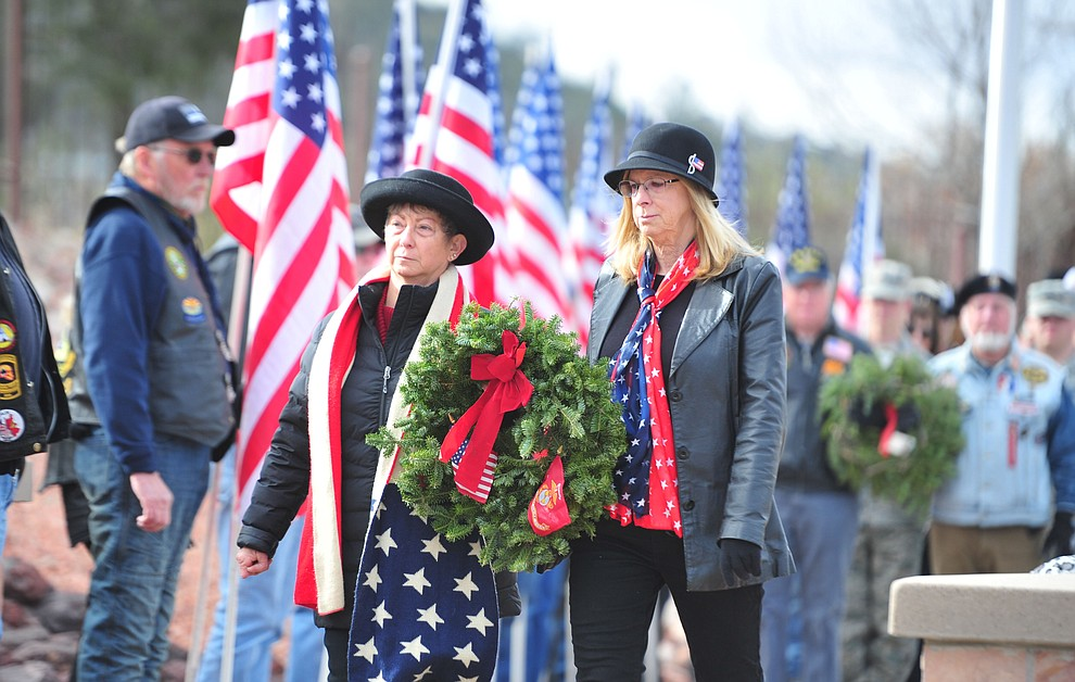 Darlene Packard and Loyce Johnston place a wreath to honor those that served or are serving in the United States Marine Corps during the Wreaths Across America ceremony where 2106 veteran remembrance wreaths at the Prescott National Cemetery Saturday, Dec. 15, 2018. (Les Stukenberg/Courier).