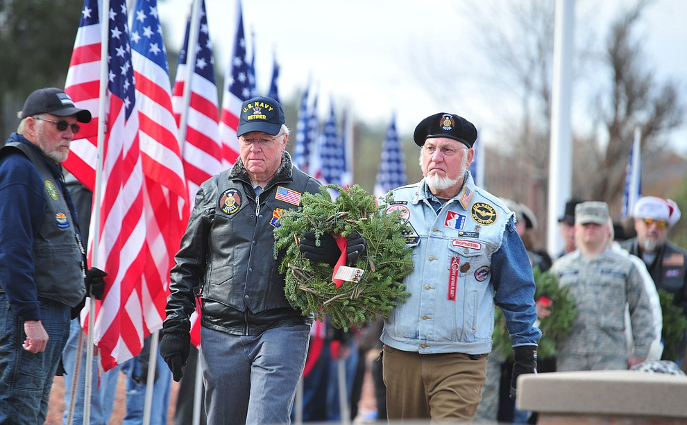 Navy veterans Mike Ammons and Bob Meadowcraft place a wreath to honor those that served or are serving in the United States Navy during the Wreaths Across America ceremony where 2106 veteran remembrance wreaths at the Prescott National Cemetery Saturday, Dec. 15, 2018. (Les Stukenberg/Courier).