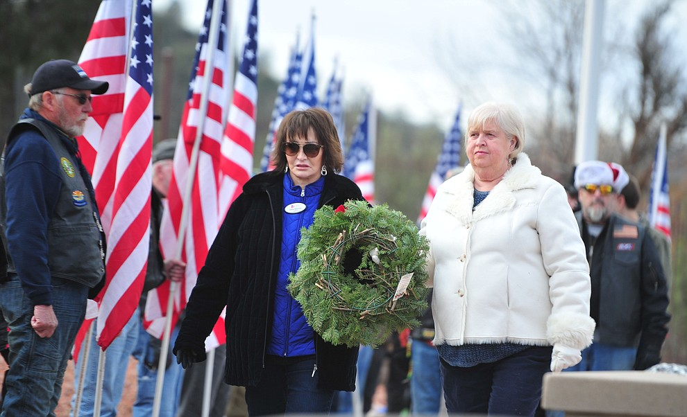 Lynda Avey and Kathy Machmer place a wreath to honor those that served or are serving in the United States Coast Guard during the Wreaths Across America ceremony where 2106 veteran remembrance wreaths at the Prescott National Cemetery Saturday, Dec. 15, 2018. (Les Stukenberg/Courier).