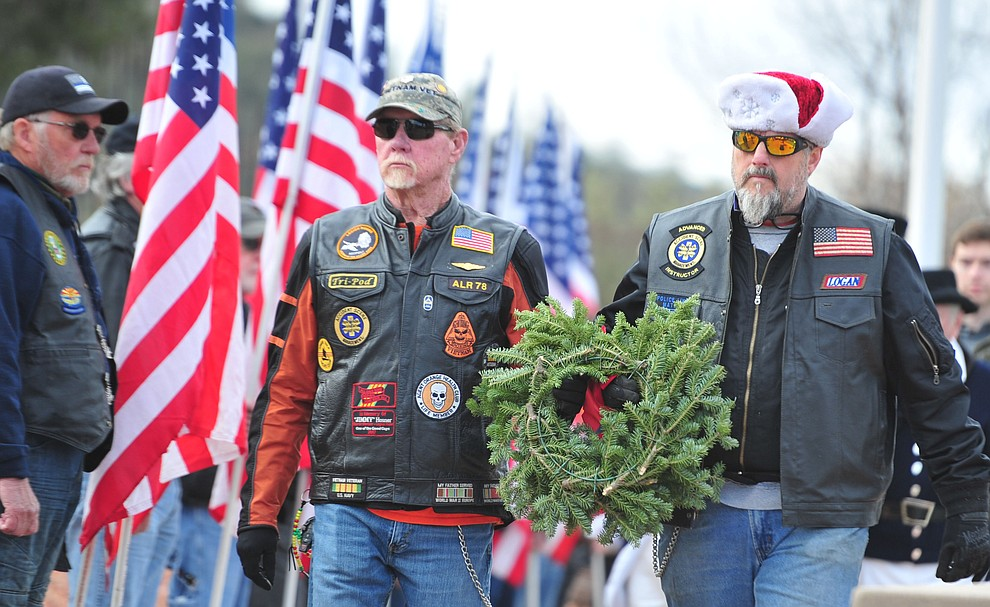 Vietnam veterans David Legat and Logan Roberts place a wreath to honor those that served or are serving in the United States Merchant Marines during the Wreaths Across America ceremony where 2106 veteran remembrance wreaths at the Prescott National Cemetery Saturday, Dec. 15, 2018. (Les Stukenberg/Courier).