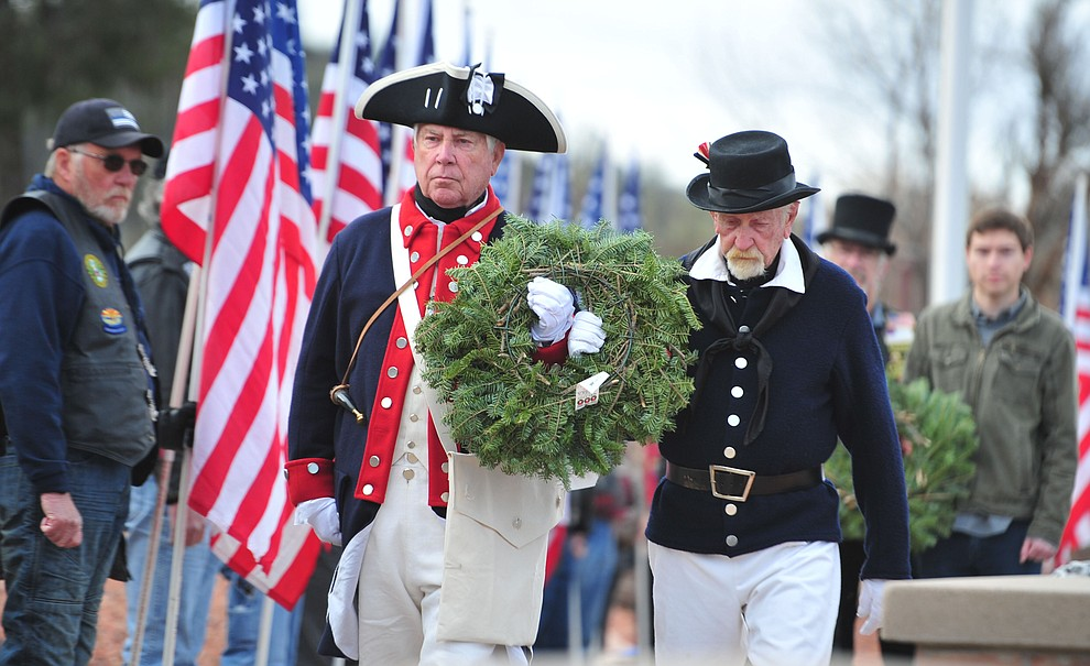 US Navy veteran Jim Laurensen and US Army veteran Eugene McCarthy place a wreath to honor those veterans we lose every day to suicide during the Wreaths Across America ceremony where 2106 veteran remembrance wreaths at the Prescott National Cemetery Saturday, Dec. 15, 2018. (Les Stukenberg/Courier).