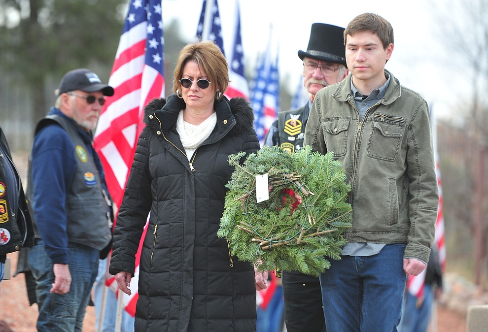 Gold Star Mother Diane Sowinski and her son Austin place a wreath to honor those service members whose last known status was either prisoner of war or missing in action  during the Wreaths Across America ceremony where 2106 veteran remembrance wreaths at the Prescott National Cemetery Saturday, Dec. 15, 2018. (Les Stukenberg/Courier).