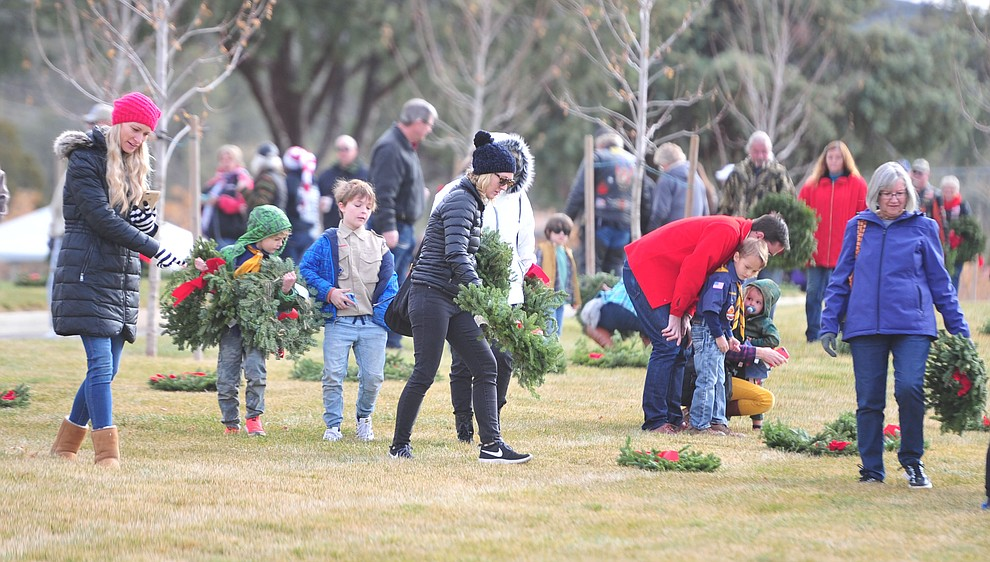 People place wreaths during the Wreaths Across America ceremony where 2106 veteran remembrance wreaths at the Prescott National Cemetery Saturday, Dec. 15, 2018. (Les Stukenberg/Courier).