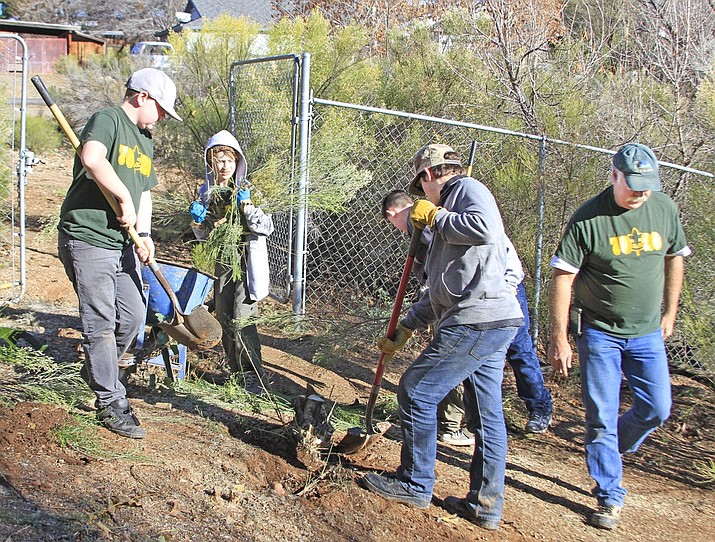 From left, Boy Scouts Shaun Harmon Jr., Wil Luhman, background is Bronsen Harvey, foreground is Elias Kline, and Scoutmaster Chris Beisecker, Troop 7020, clearing the trail and digging up roots around Sunset Lake (also known as the Duck Pond).