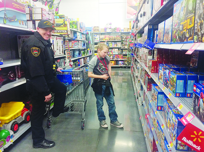 Prescott Valley Police Officer Brandon Kelly and Kobe look at toys during the 21st annual Shop with a Cop event Saturday, Dec. 15, 2018. Kelly participated in the inaugural local Shop with a Cop event as one of the kids. (Jason Wheeler/Courier)