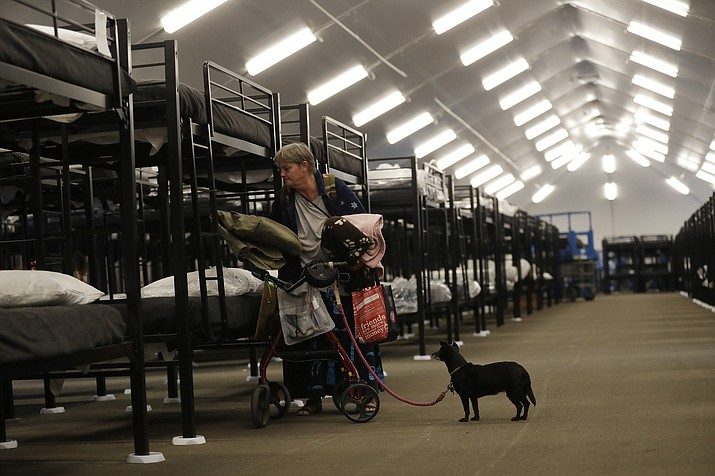 Verna Vasbinder prepares her new bunk in the city's new Temporary Bridge Shelter for the homeless as her dog, Lucy Lui, looks on in San Diego in Dec. 1, 2017. A new federal report says the number of people living on the streets in Los Angeles and San Diego, two epicenters of a West Coast homelessness crisis, fell this year, suggesting possible success in those cities' efforts to combat the problem. (Gregory Bull/AP, File)