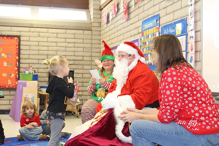 A preschooler at La Senita School thanks Santa Claus in American Sign Language during the deaf Santa's visit to the school Tuesday. (Photo by Hubble Ray Smith/Daily Miner)