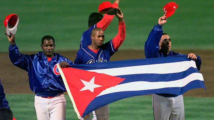 In this Monday, May 3, 1999 file photo, members of the Cuban baseball team carry their country's flag onto the field after a baseball game against the Baltimore Orioles at Camden Yards in Baltimore. Major League Baseball, its players' association and the Cuban Baseball Federation reached an agreement that will allow players from the island nation to sign big league contracts without defecting, an effort to eliminate the dangerous trafficking that had gone on for decades. The agreement runs through Oct. 31, 2021. (Nick Wass/AP, File)