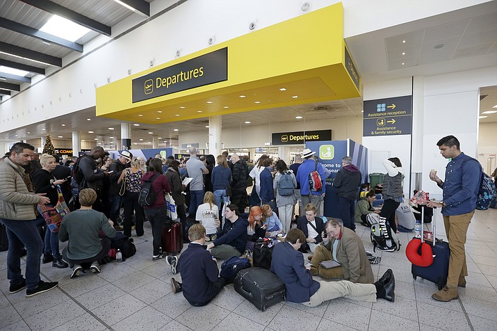 People wait outside the departures gate at Gatwick airport, near London, as the airport remains closed with incoming flights delayed or diverted to other airports, after drones were spotted over the airfield last night and this morning, Thursday, Dec. 20, 2018. (AP Photo/Tim Ireland)