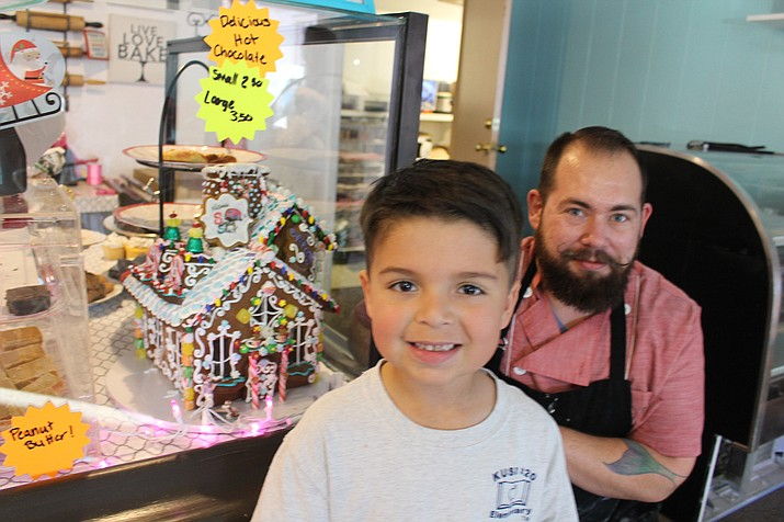 Gideon Eads, manager and decorator of Victoria's Sugar Shack bakery in Kingman, created this colorful gingerbread house in the display case that caught the eye of 5-year-old Adam. (Photo by Hubble Ray Smith/Daily Miner)