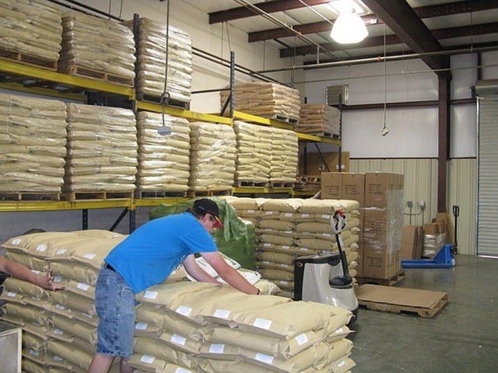YEI guy Austin stacks bags of raw bird seed in the YEI! warehouse, which YEI guys and gals will later mix (into special, proprietary blends) and package for Jay's Bird Barn in Prescott. (Courtesy)