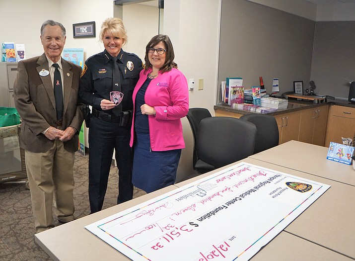 Prescott Police Foundation President Michael Broggie, left, Prescott Police Chief Debora Black, center, and YRMC Breast Care Center Manager Kathi Hoffer celebrate a $3,511 donation that the foundation presented to the Breast Care Center on Dec. 20. (Cindy Barks/Courier)