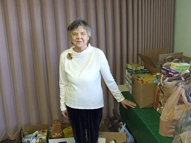 Linda Schall-Rhodes stands with food collected by Kingman Presbyterian Church for the Kingman Area Food Bank. It's the third year of the church's food drive, which was started by Schall-Rhodes' late husband, Jason. (Courtesy)