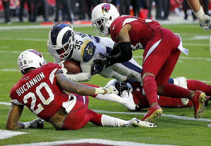 Los Angeles Rams running back C.J. Anderson (35) scores a touchdown as Arizona Cardinals outside linebacker Deone Bucannon (20) and Arizona Cardinals defensive back David Amerson defend during the first half of an NFL football game, Sunday, Dec. 23, 2018, in Glendale. (Rick Scuteri/AP)