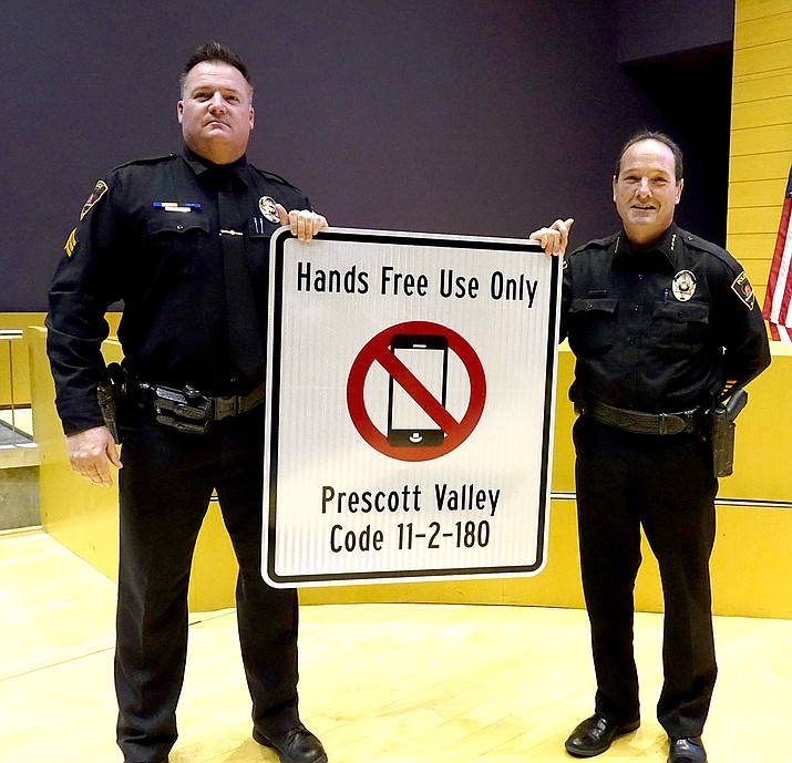 Prescott Valley Police Chief Bryan Jarrell, right, and Sgt. Rob Brown hold up one of seven new signs indicating the town's ordinance prohibiting the use of handheld communication devices after the Dec. 20 town council meeting. (Town of Prescott Valley/Courtesy)