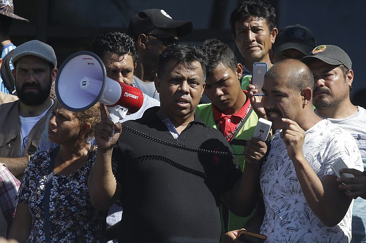 Migrant activist Irineo Mujica, center, of the group Pueblo Sin Fronteras or People Without Borders, holds a megaphone as a Central American migrant speaks to reporters during a press conference Oct. 22, 2018, in Tapachula, Mexico. (Moises Castillo/AP)