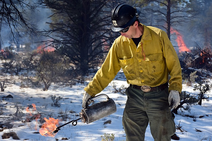 Kaibab N.F. fire personnel, Brandon Oberhardt using a drip torch to light a pile burn on the Tusayan Ranger District. (Photo by Dyan Bone, U.S. Forest Service Kaibab National Forest)