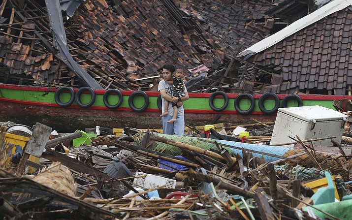 A man holding a child looks the damage at a tsunami-ravaged village in Sumur, Indonesia, Tuesday, Dec. 25, 2018. The Christmas holiday was somber with prayers for tsunami victims in the Indonesian region hit by waves that struck without warning Saturday night.(Achmad Ibrahim/AP)