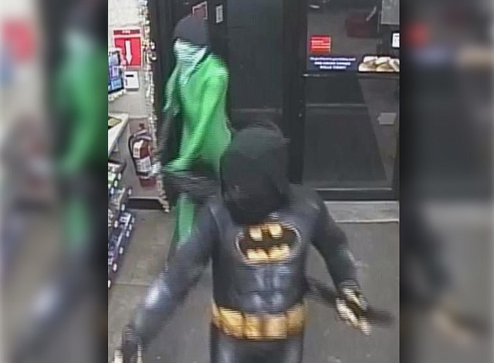 Surveillance photos show the costumed men approach the convenience store counter and force the clerk to fill a bag with cash before running out the back door. (Council Bluffs Police Department)