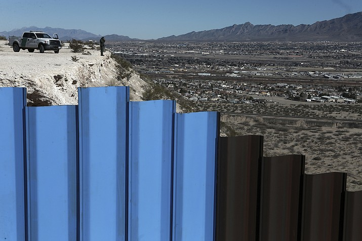 In this Jan. 25, 2017, file photo, an agent from the border patrol, observes near the Mexico-US border fence, on the Mexican side, separating the towns of Anapra, Mexico and Sunland Park, N.M. An 8-year-old boy from Guatemala died in government custody early Tuesday, Dec. 25, 2018, U.S. immigration authorities said. (AP Photo/Christian Torres, File)