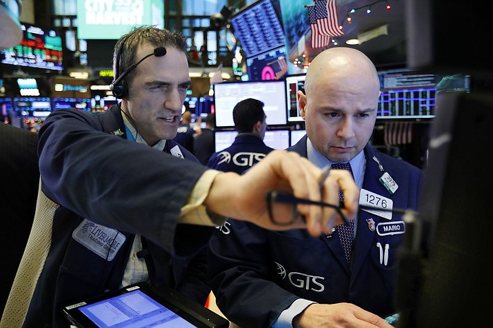 Trader Gregory Rowe, left, and specialist Mario Picone work on the floor of the New York Stock Exchange, Thursday, Dec. 27, 2018. Wall Street's wild Christmas week goes on, with the Dow Jones Industrial Average slumping 300 points at the open Thursday, a day after notching its biggest-ever point gain. (Richard Drew/AP)