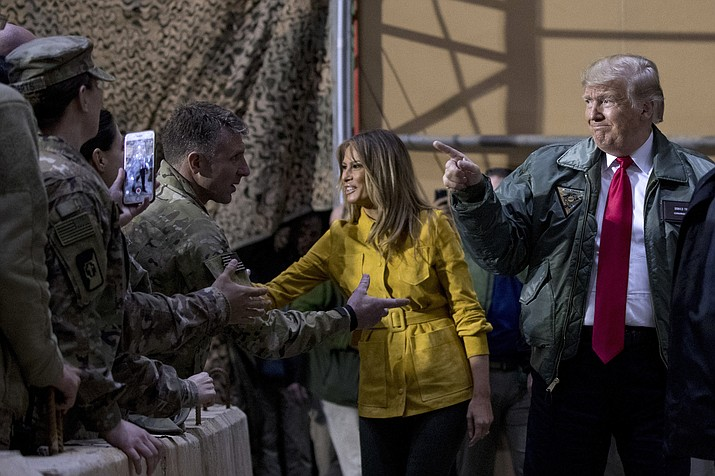 President Donald Trump and first lady Melania Trump greet members of the military as they arrive for a hangar rally at Al Asad Air Base, Iraq, Wednesday, Dec. 26, 2018. In a surprise trip to Iraq, President Donald Trump on Wednesday defended his decision to withdraw U.S. forces from Syria where they have been helping battle Islamic State militants. (Andrew Harnik/AP)
